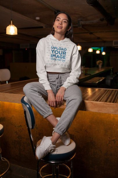 Crop Top Hoodie Mockup Featuring a Woman Sitting over a Wooden Bar 26103