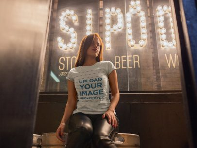 T-Shirt Mockup of a Seductive Girl Sitting in Front of a Bright Sign 18022