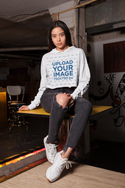 Crop Top Hoodie Mockup Featuring a Girl Sitting over an Old Bar's Table 26105