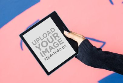Mockup of a Woman Holding a Kindle Oasis Mockup Against a Colorful Surface 26150