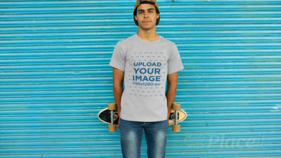 T-Shirt Video of a Young Man Holding a Skateboard Behind His Back 12870