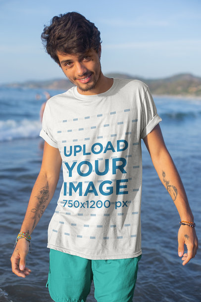 Mockup of a Tattooed Young Man by the Sea Wearing a T-Shirt