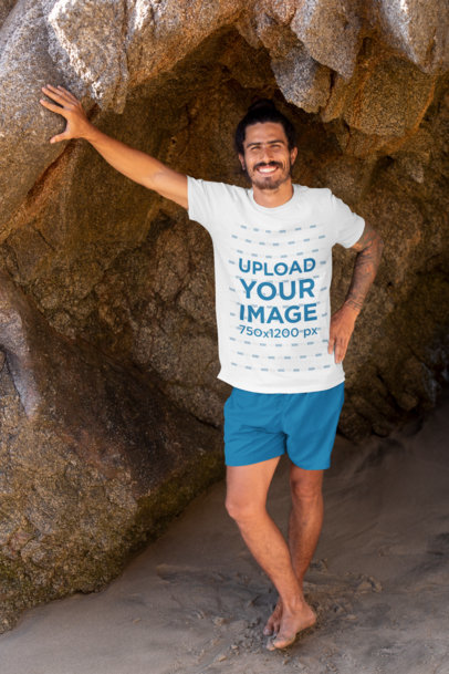 T-Shirt Mockup of a Tattooed Man Leaning Against a Big Rock by the Beach 26804