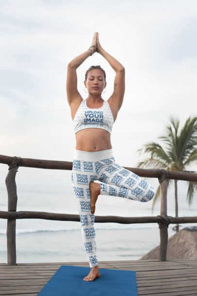 Mockup of a Woman with a Sports Bra and Leggings Doing Yoga by the Sea 26859