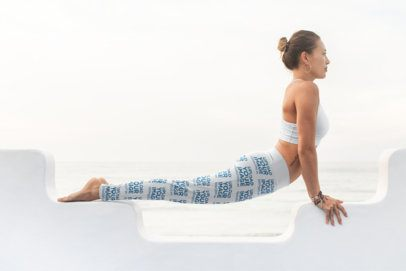 Mockup of a Woman in a Sports Bra and Leggings Practicing Yoga by the Ocean 26860