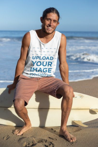 Tank Top Mockup of a Smiling Man with Tied Hair Sitting over His Surfboard at the Beach 26758