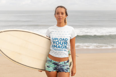 T-Shirt Mockup of a Young Woman with a Ponytail Carrying a Surfboard at the Beach 26830