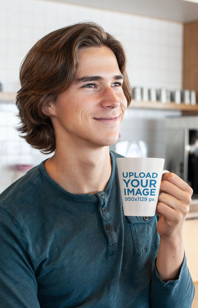 Coffee Mug Mockup of a Smiling Young Man in a Kitchen 26515