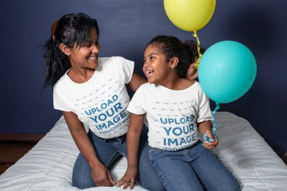 T-Shirt Mockup of a Smiling Mommy and Her Daughter Holding Balloons over a Bed 26387