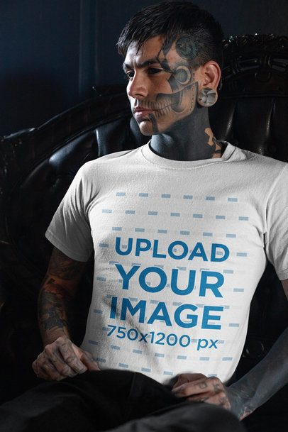 T-Shirt Mockup of a Goth Man with Tattoos All over His Body Sitting in a Dark Armchair 26603