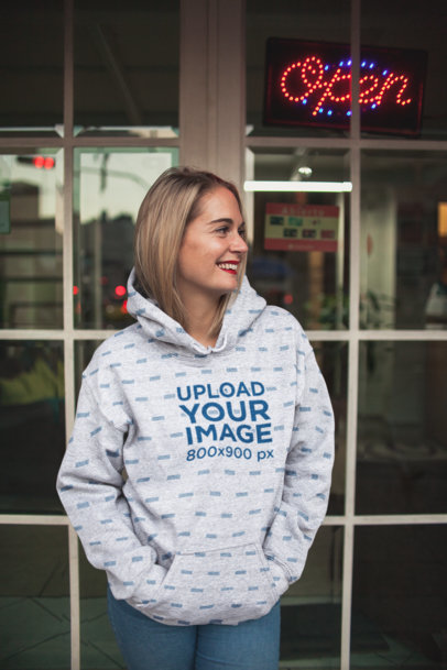 Hoodie Mockup of a Blonde Woman Standing Next to a Window Pane 23980