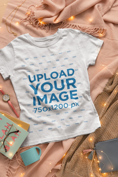 Flat Lay T-Shirt Mockup over a Cooper Soft Fabric Surrounded by Fairy Lights 26548