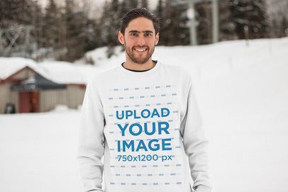 Mockup of a Man with a Beard Wearing a Sweatshirt on a Snowy Mountain 25108