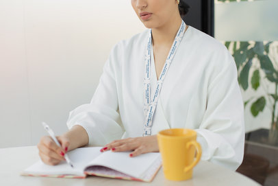 Lanyard Mockup of a Woman Taking Notes at Work