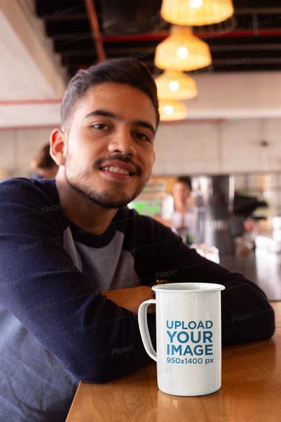 Mockup of a 21 Oz Mug over a Countertop Next to a Smiling Man  26938