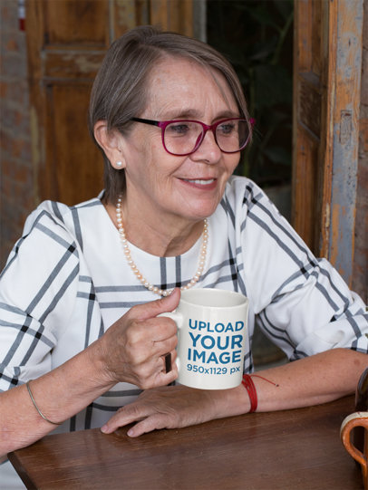 Mockup of an Elderly Woman Holding an 11 Oz Coffee Mug at a Table 27455