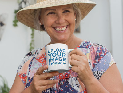 Mockup of a Joyful Senior Woman Wearing a Hat and Holding Her 11 Oz Coffee Mug 27457
