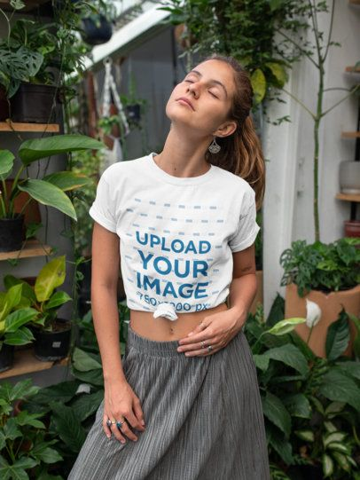 Mockup of a Young Woman Wearing a Knotted T-Shirt by Some Plants 27090