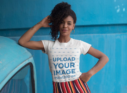 Tee Mockup of a Cool Woman with Curly Hair Posing in Front of a Blue Wall 27348