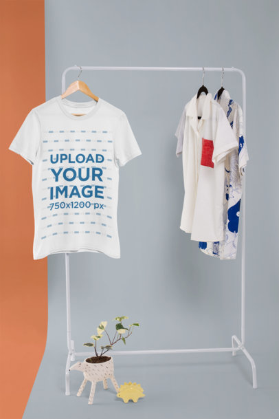 T-Shirt Mockup Hanging from a Rack Along with Other Garments 26738