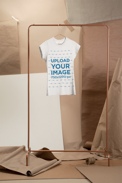 Mockup of a Women's T-Shirt Hanging from a Clothing Rack in Front of a Kraft Paper Backdrop 27483