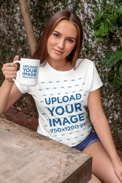 Mockup of a Woman with a Crewneck T-Shirt Holding a 15 oz Mug at a Concrete Table 27512