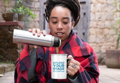 Mockup of a Woman with a Checkered Blanket Pouring Coffee into a 21 oz Enamel Mug 26981