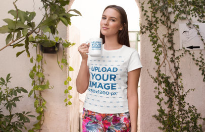 T-Shirt Mockup of a Woman Holding a 15 oz Mug Against a Wall Covered in Plants 27514