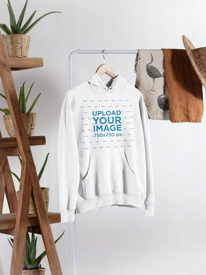 Pullover Hoodie Mockup Hanging From a Rack Next to Plant Pots 27391