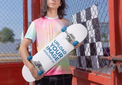 Mockup of a Skater Man Holding a Skateboard 27197
