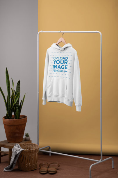 Women's Pullover Hoodie Mockup Hanging from a Simple Rack by a Plant Pot 27490