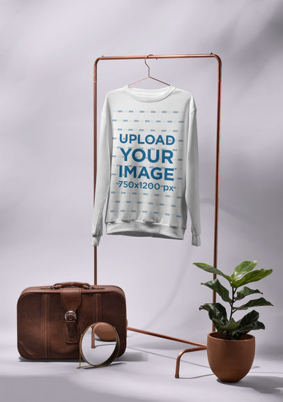 Mockup of a Men's Crewneck Sweatshirt Hanged Next to a Vintage Suitcase 27401