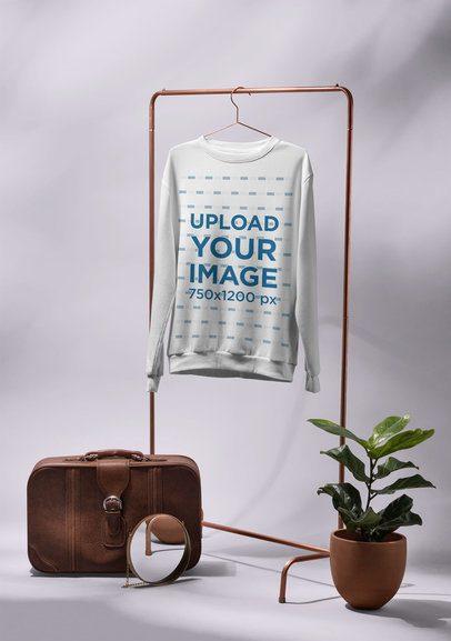 Mockup of a Men's Crewneck Sweatshirt Hanged Next to a Vintage Suitcase 27401