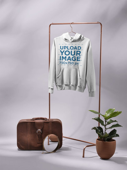 Minimalistic Mockup of a Pullover Hoodie Hanging Next to a Plant Pot and a Vintage Suitcase 27411
