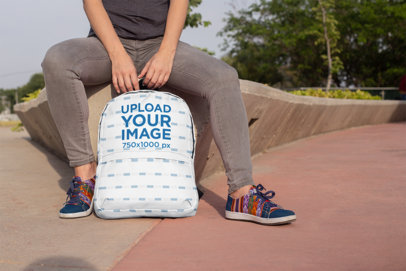 Backpack Mockup Featuring a Student Sitting on a Concrete Planter 27699