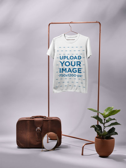 T-Shirt Mockup Hanging From a Rack Next to a Vintage Suitcase and a Plant 27409
