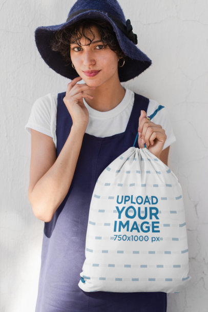 Mockup of a Woman with a Floppy Hat and an Overall Holding a Drawstring Bag 27584