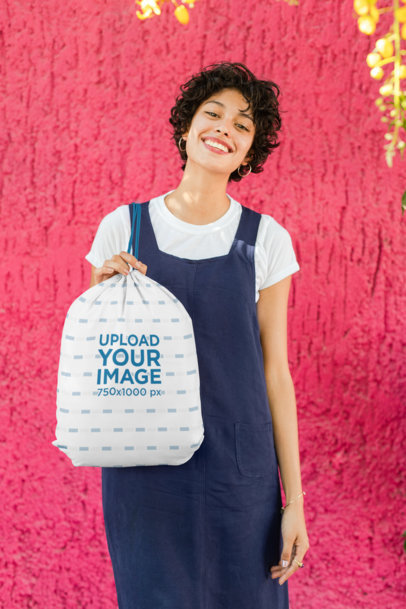 Drawstring Bag Mockup Featuring a Smiling Woman Against a Bright Wall 27585