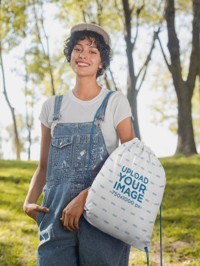 Drawstring Bag Mockup Featuring a Woman Wearing a Denim Overall in the Woods 27591