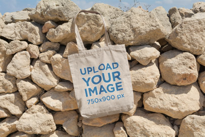 Mockup of a Tote Bag Lying on a Bunch of Rocks 13-el
