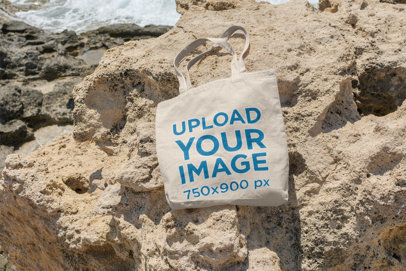 Mockup of a Tote Bag Lying on a Rock by the Sea 17-el
