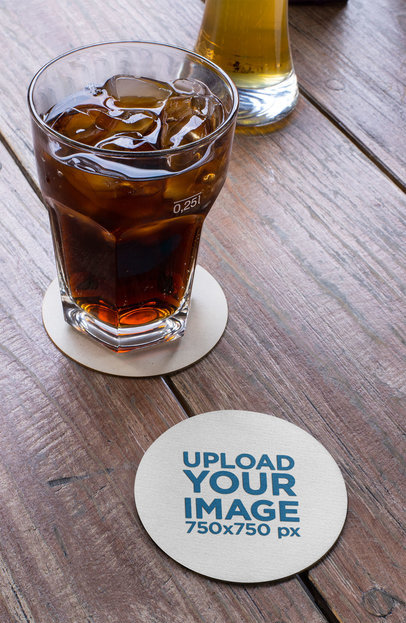 Mockup of a Round Coaster by a Cola Drink over a Wooden Table 27809