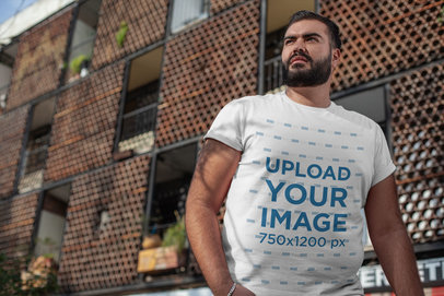 Plus Size T-Shirt Mockup of a Bearded Man Posing Against a Modern Building 27753