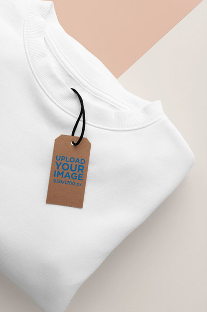 Mockup of a Cardboard Clothing Tag Lying on a Sweater over a Two Color Background 27640