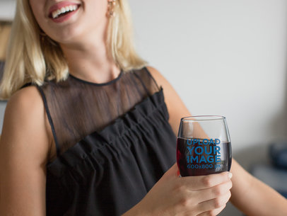 Mockup of a Blonde Woman Holding a Stemless Wine Glass 27933