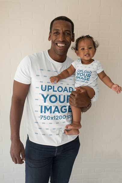 Mockup of a Smiling Man with a T-Shirt Holding Her Baby Girl in a Onesie 28067