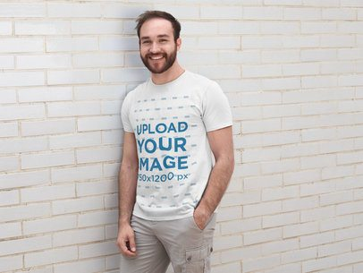 T-Shirt Mockup of a Young Man Leaning Against a White Wall 28188