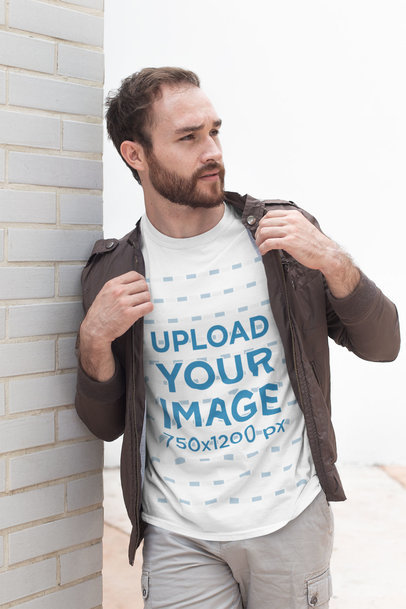 Shirt Mockup of a Bearded Man Leaning Against a White Brick Wall