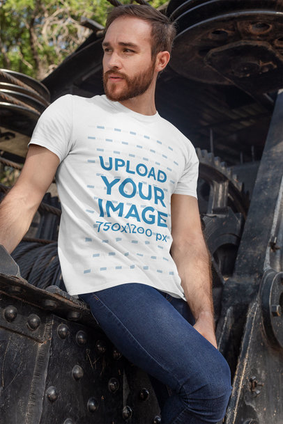 Tee Mockup Featuring a Bearded Man Leaning Against Some Old Industrial Machinery 28191