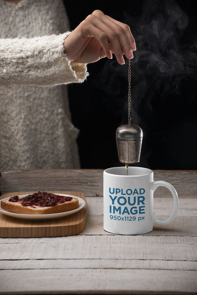 Mockup of an 11 oz Mug with a Tea Infuser on a Wooden Table 28173
